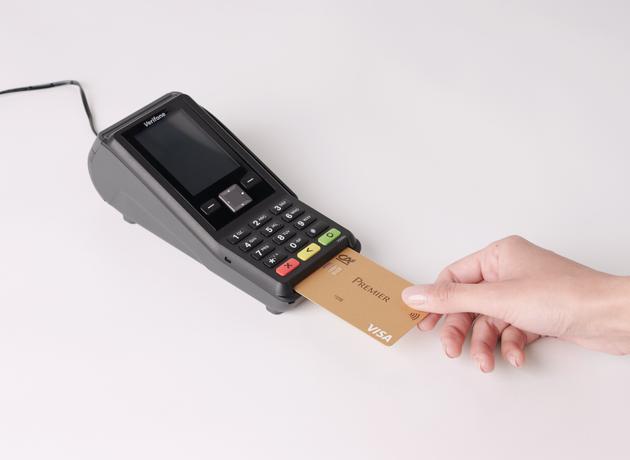 Terminal de paiement avec fil et avec main insérant une carte gold