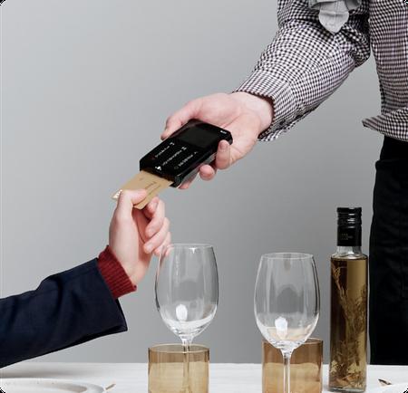 Terminal de paiement avec main insérant une carte gold