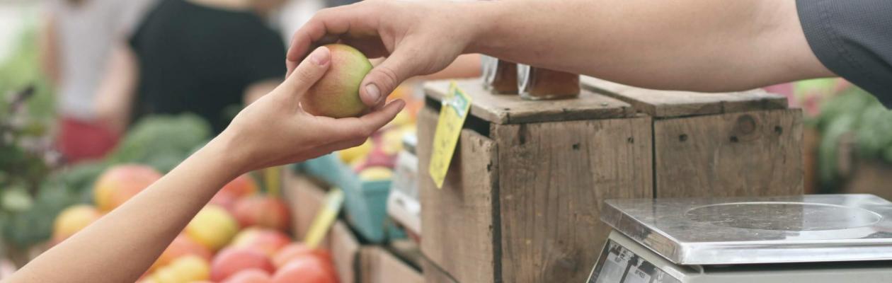 Maraîcher tendant une pomme à sa cliente