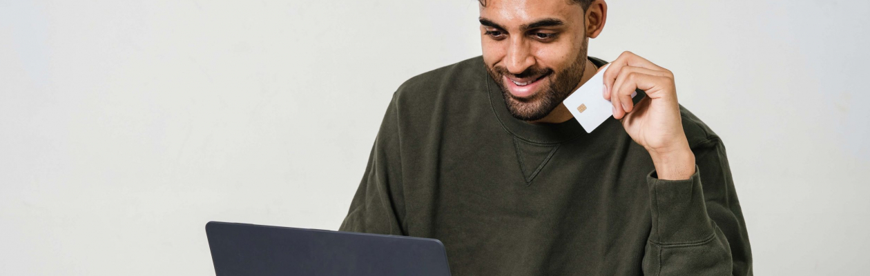 Homme avec carte bleu devant son ordinateur